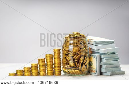Savings Growth Or Successful Investment. Pile Of Gold Coins With Steps And Glass Jar Full Of Coins.