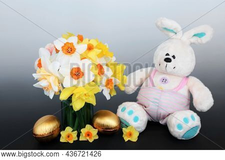 Easter bunny with golden eggs, daffodil flowers in a vase. Symbols of Easter and Spring fun concept on gradient grey background.
