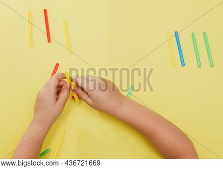 A Small Child Collects A Geometric Figure From Counting Sticks. Childrens Hands With Counting Sticks