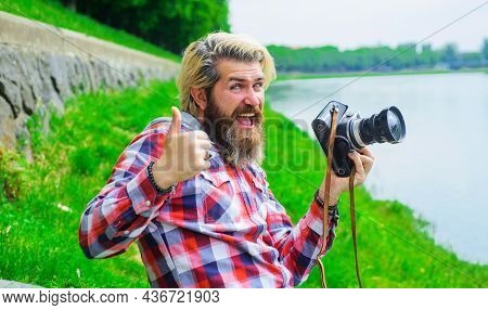 Bearded Man Taking Photo With Camera On River. Hobby And Travel. Smiling Man With Professional Digit