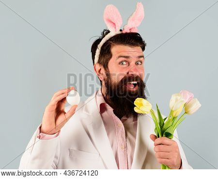 Bearded Man Preparing For Easter. Eggs Hunt. Rabbit Man. Smiling Bearded Man In Suit With Egg And Fl