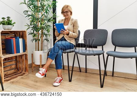 Middle age blonde woman smiling confident using touchpad at waiting room