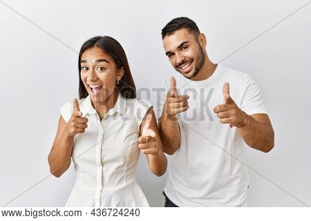 Young interracial couple standing together in love over isolated background pointing fingers to camera with happy and funny face. good energy and vibes.