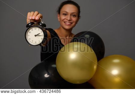 Focus On The Hand Holding A Black Alarm Clock Of A Blurred Woman Smiling Toothy Smile Holding Gold B