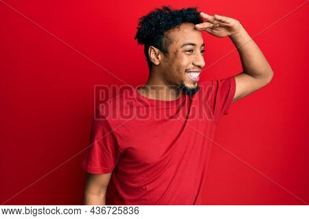 Young african american man with beard wearing casual red t shirt very happy and smiling looking far away with hand over head. searching concept.