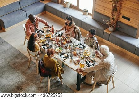 High angle view of big family sitting at dining table and having dinner together in dining room at home