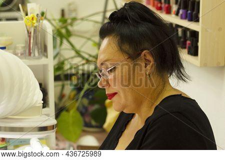 The Manicure Process. Cosmetic Procedure, Beauty Salon. A Beautiful, Bright Woman, A Manicure Specia