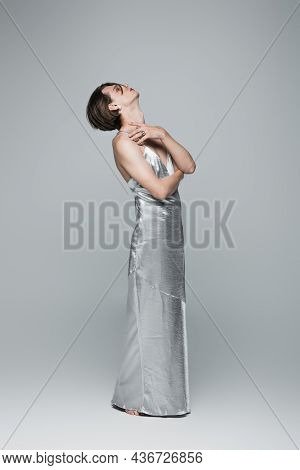Full Length Of Young Transgender Man In Slip Dress Looking Up While Posing On Gray