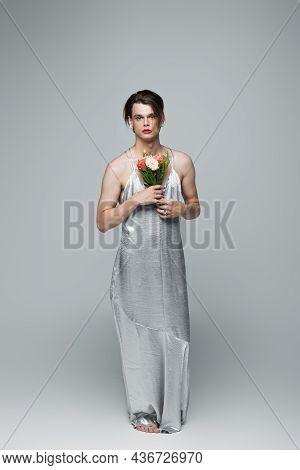 Full Length Of Transgender Man In Slip Dress Posing With Flowers On Gray