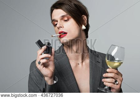 Young Transgender Man In Blazer Holding Glass Of Wine And Lighter While Smoking Isolated On Grey