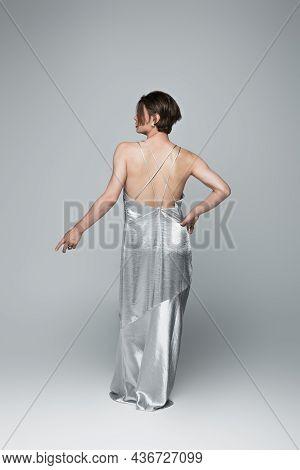 Full Length Of Transgender Man In Slip Dress Posing With Hand On Hip On Gray