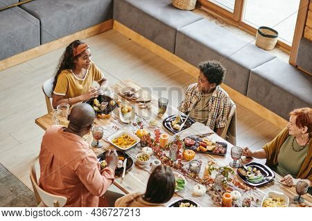 High angle view of big family sitting at holiday table in the dining room and talking to each other