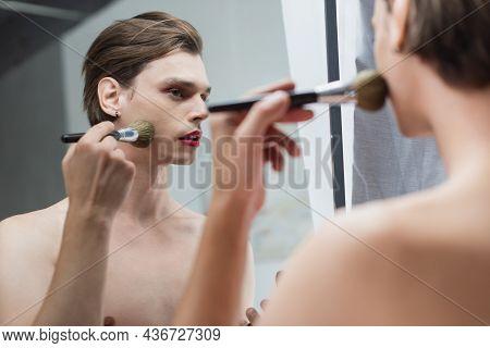 Young Transgender Man Applying Face Powder Near Mirror