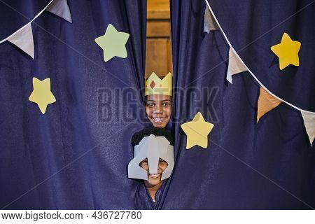 Portrait of children in costumes smiling at camera hiding behind the scenes, they acting in performance