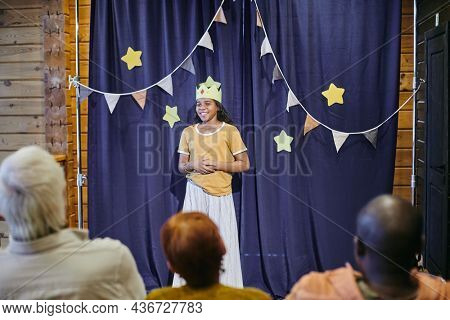 African girl in carton crown acting on the scene she showing the performance for people