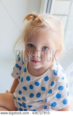 Close Up Portrait Of Adorable Baby Girl Sitting On The Windowsill