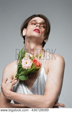 Young Transgender Man In Slip Dress Posing With Flowers Isolated On Gray