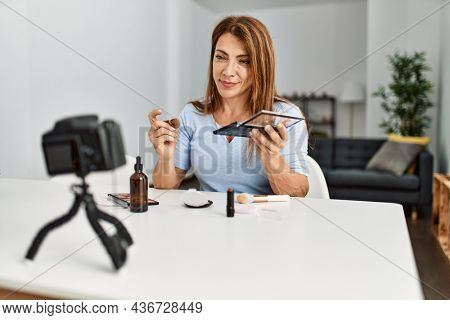 Middle age caucasian woman making makeup tutorial using camera sitting on the table at home.