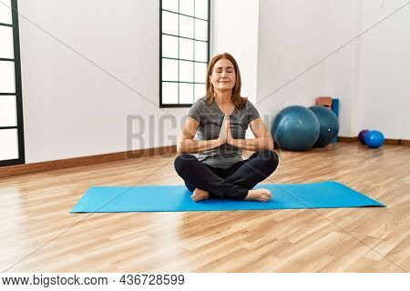 Middle age caucasian woman smiling confident training yoga at sport center