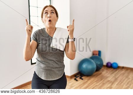 Middle age woman wearing sporty look training at the gym room amazed and surprised looking up and pointing with fingers and raised arms.