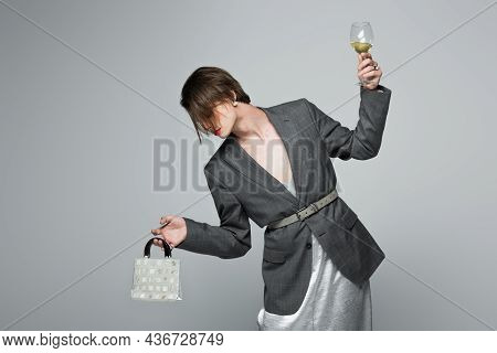 Young Transgender Man In Slip Dress With Blazer Holding Purse And Glass Of Wine Isolated On Grey