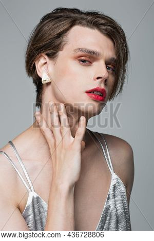 Young Transgender Man With Makeup And Earring Posing Isolated On Grey