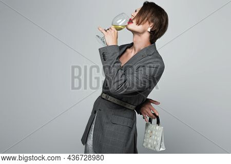 Transgender Man In Blazer Drinking Wine While Holding Purse Isolated On Gray