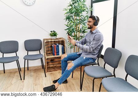Young arab man listening to music sitting on chair at waiting room