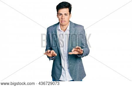 Young hispanic man wearing business clothes disgusted expression, displeased and fearful doing disgust face because aversion reaction.