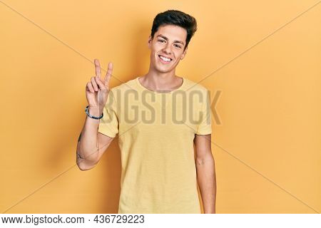 Young hispanic man wearing casual yellow t shirt smiling looking to the camera showing fingers doing victory sign. number two.
