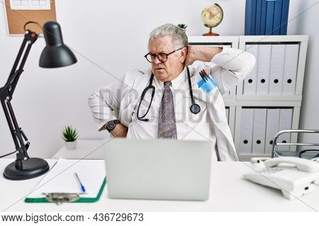 Senior caucasian man wearing doctor uniform and stethoscope at the clinic suffering of neck ache injury, touching neck with hand, muscular pain