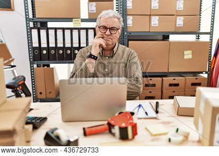 Senior caucasian man working at small business ecommerce with laptop with hand on chin thinking about question, pensive expression. smiling with thoughtful face. doubt concept.