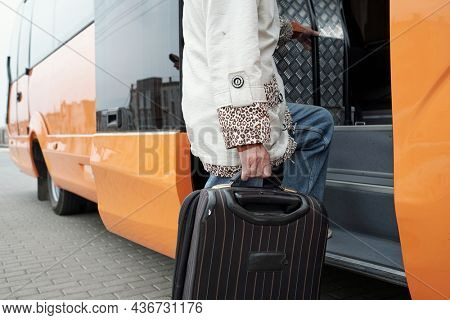Contemporary senior passenger with suitcase putting leg on staircase while entering bus