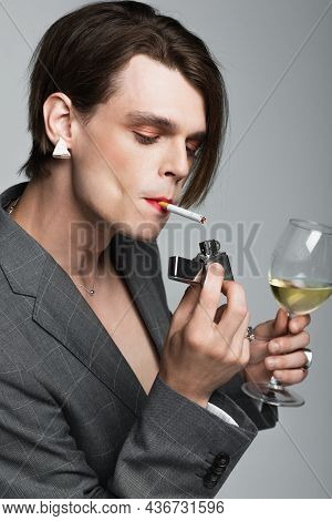 Young Transgender Man Holding Glass Of Wine And Lighter While Smoking Isolated On Grey