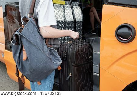 Young female with backpack on shoulder holding suitcase while entering intercity bus