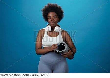 Young pretty African sportswoman with rolled mat standing against blue background