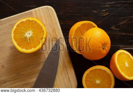 Oranges, Cut In Half, Lie On A Cutting Kitchen Board On A Wooden Table. Preparing Freshly Squeezed O