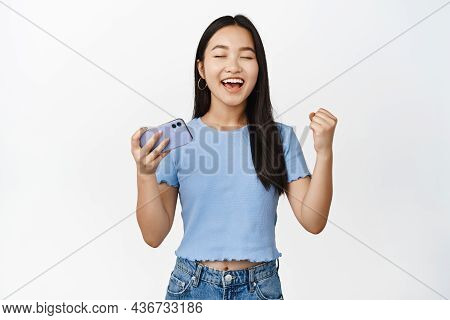 Enthusiastic Smiling Asian Woman Winning On Mobile Phone Video Game, Looking Satisfied And Relieved,