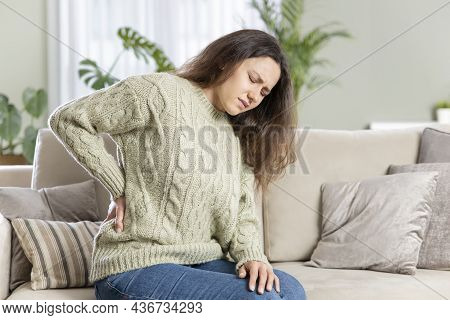 Young Woman Suffering With Back Pain, Sitting On A Couch And Holding Her Lower Back With Hand. Axial