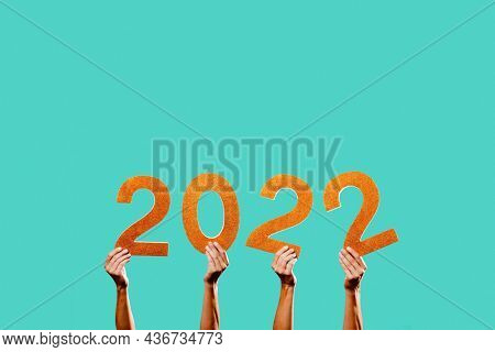men hands holding some golden three-dimensional numbers forming the number 2022, as the new year, on a blue background with some blank space on top