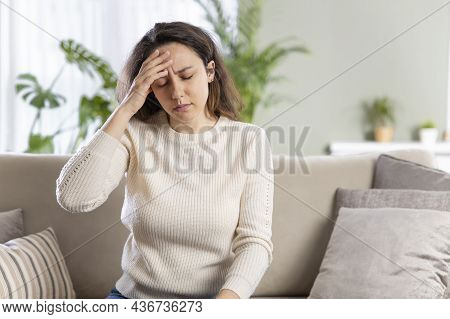 Young Woman With Headache Sitting On Sofa. General Health Problems Concept - Migraine.