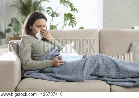 Portrait Of Ill Woman Caught Cold, Feeling Sick And Sneezing In Paper Wipe. She Covered In Blanket W