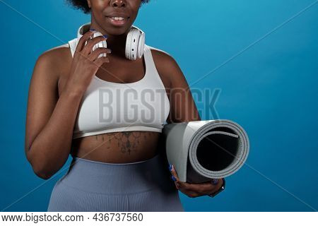 Young active sportswoman with rolled mat and headphones standing in front of camera