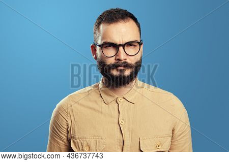 Man Wears Beige Sweater And Eyeglasses, Has Serious Expression, Tries To Come Up With Solution. Jeal