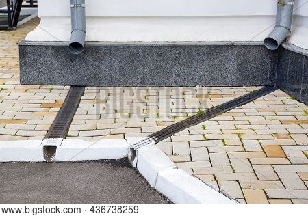 Facade Of A Building Wall With A Downspout Pipe And A Concrete Dish Canal With Iron Grid On A Stone