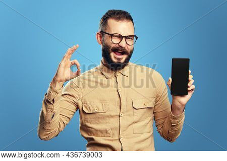 Young Man Wearing Beige Shirt And Eyeglasses Blinks Eye And Showing Blank Screen Mobile Phone While