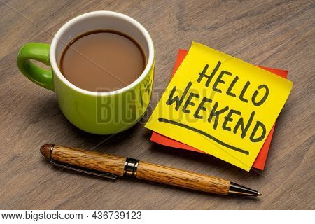 hello weekend - handwriting on a sticky note with a cup of coffee, cheerful message