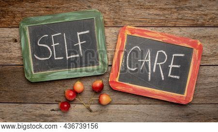 self care - white chalk handwriting on a retro slate blackboards against weathered wood - mental, emotional, and physical health concept