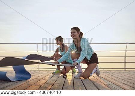 Young fit girls spread out fitness mats for workout. Sporty caucasian females in sportswear preparing for exercising on wooden platform at sunrise. Two girlfriends doing sport on sunny day