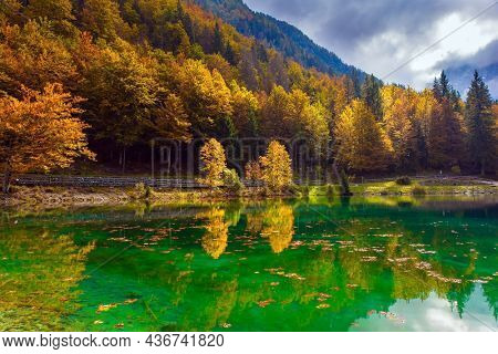 Lake Fuzine. Grand mountain range Dolomite Alps. Border between Northern Italy and Slovenia. Orange, yellow and red trees are reflected in the green smooth water of the lake.